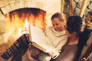 Mom with child reading book and relaxing by the fire place some cold evening, winter weekends, cozy scene